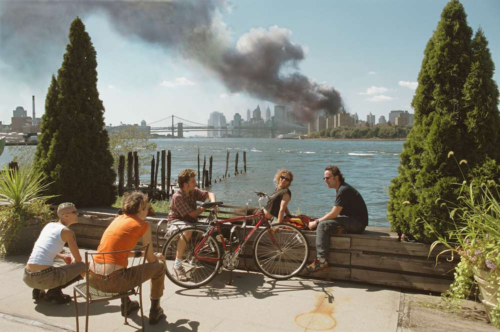USA. Brooklyn, New York. September 11, 2001. Personas tomándose una foto relajadas mientras sube la nube de humo de los ataques al World Trade Center.